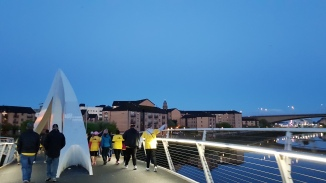 A woman throws a yellow flower over the side of the Tradeston Bridge