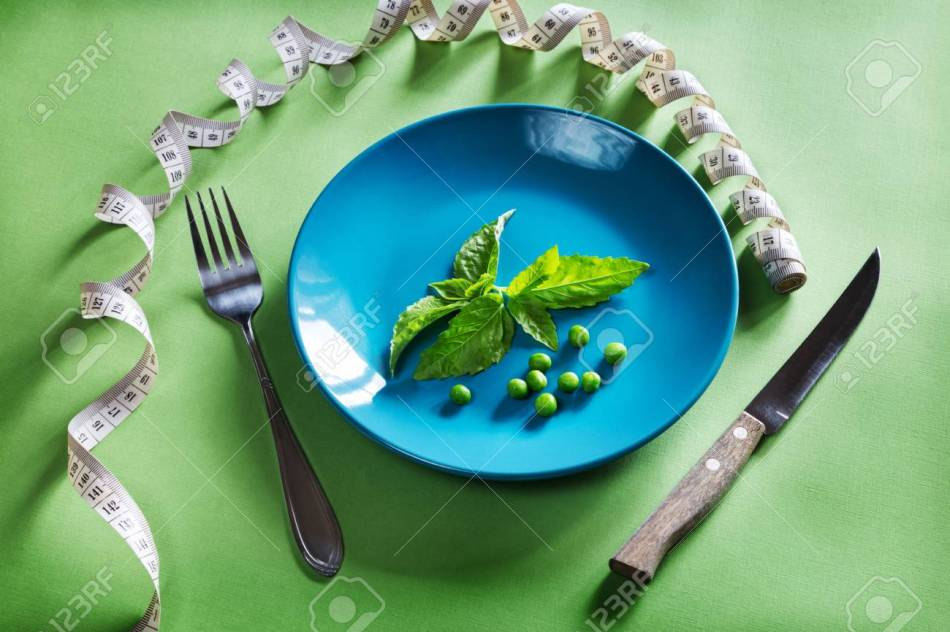 Diet blue plate with centimeter, basil and peas